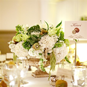 "A rustic, vintage-looking urn was filled with white hydrangeas, kale, green amaranthus and kiwis at the ""Kiwi"" table."