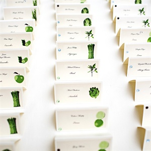 The tented escort cards featured guests&#39; names and a green picture of their table&#39;s fruit or veggie.