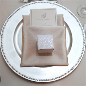 The place settings were elegantly laid out with favor boxes on top of the napkins which were made by the bride's mother. She had luggage tags custom-made for each guest and they were displayed at the guests' designated seats.