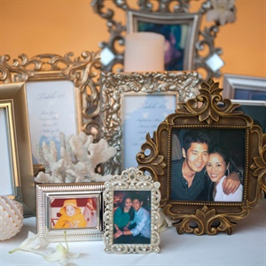 The couple set up a table with vintage frames containing seating charts as well as various photos from their childhood and as a couple.