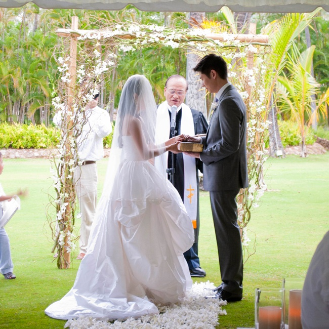 The couple married at Lanikuhonua, which means: Where Heaven Meets the Earth. It was an idyllic, private, ocean-front estate nestled within the Ko Olina resort on O'ahu.  The couple wed under a bamboo arch filled with curly willow branches and white dendrobium orchid stems.