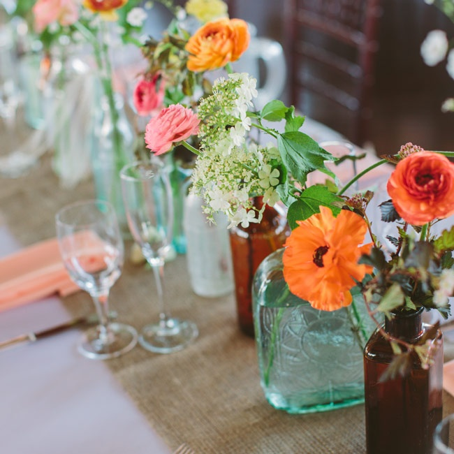 Megan and Jeff gathered bottles from flea markets leading up to the wedding and use them as vases. Each was filled with various blooms, like lady's mantle, anemones and snapdragons.