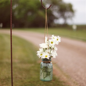 The father of the bride and her brothers created the hooks for the glass jars they filled with water and flowers to line the road to the reception.