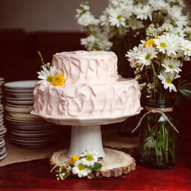 Kim and Tyler had a two tier carrot cake with light pink cream cheese frosting. The cake was decorated with daisies that fit their country casual wedding style.
