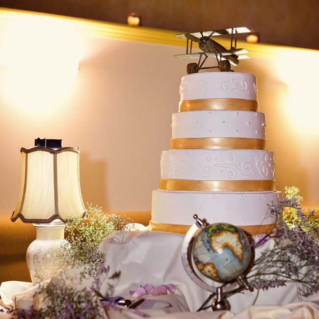 The couple's vanilla Swiss buttercream frosted cake was topped with a toy tin airplane as a nod to their travel theme.