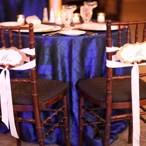 """Mr."" and ""Mrs."" signs decorated the backs of the couple's chairs."