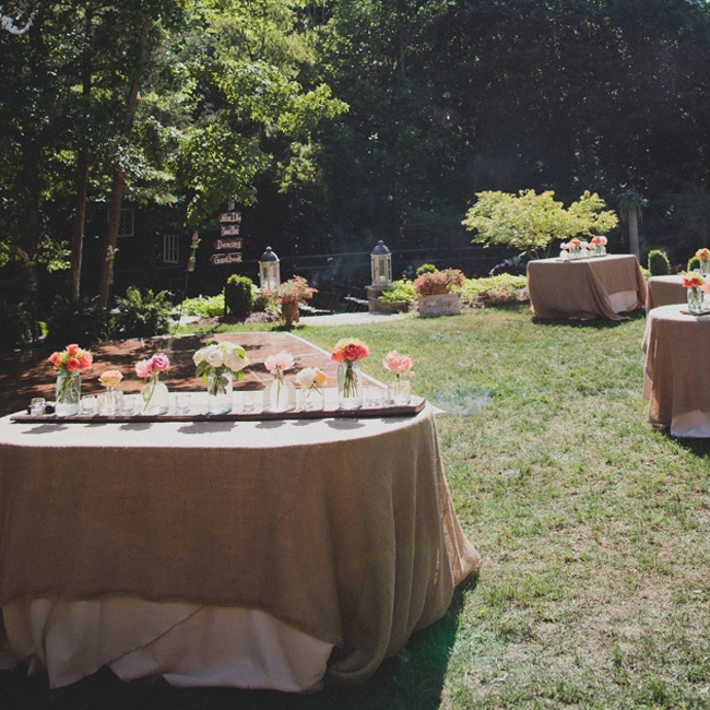 A long piece of driftwood ran down the middle of the table as a rustic runner and platform for the centerpieces, which were old mason jars and other recycled glass.The linens were floor length tan cloths with a burlap overlay.
