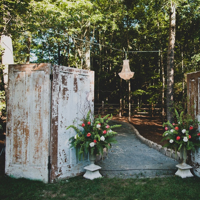 Two vintage old white doors were at the end of the aisle that framed where we got married. We also hung a large chandelier between the two doors. Two large pots of flowers on the ends of the doors became the entryway for the walkway that my groom, officiate, and best man entered from behind. There were orange, coral, pink, and white roses with hang ...