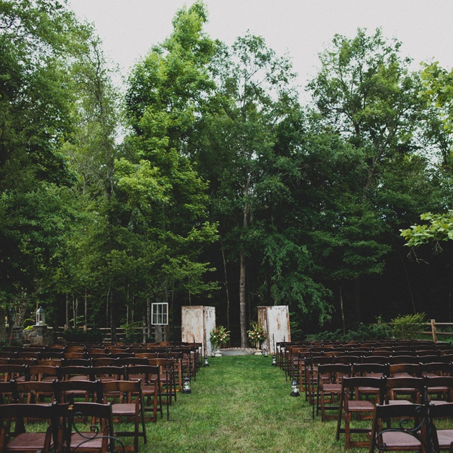 The ceremony took place in Kelsey's backyard under and they decorated the space with dark wooden chairs. At the end of every other aisle were shepherd hooks with lanterns attached at the end that had candles inside of them. Two vintage old white doors were at the end of the aisle that framed where we got married. We also hung a large chandelier bet ...