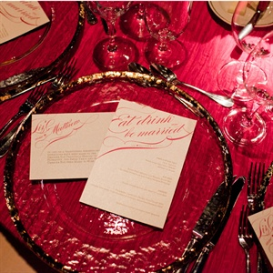 Deep red linens were topped with hammered glass gold rimmed chargers and the couples elegant menu cards.