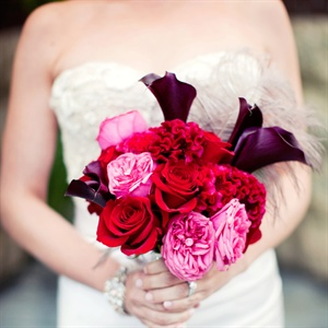 Liz carried red, purple and pink peonies, roses, calla lilies and coxcomb with feather and crystal accents.