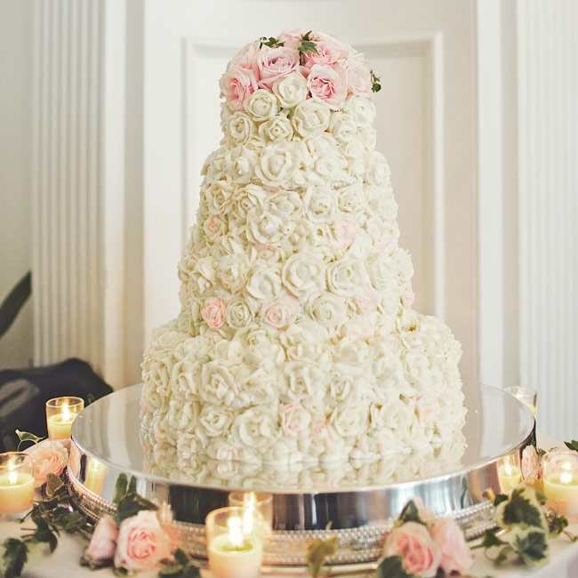Wanting their cake to look as delicious as it tasted, Elise and Brendan covered the four-tiered confection with buttercream roses and topped it off with real ones.