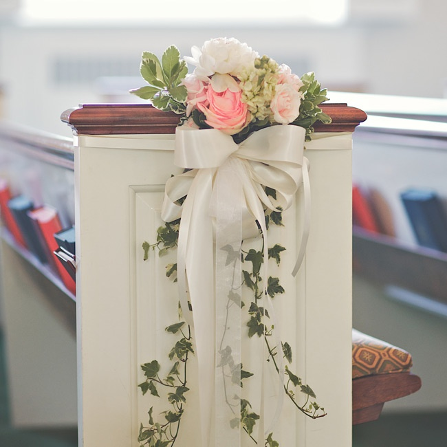 Small bunches of roses, hydrangeas and ivy decorated the pews.