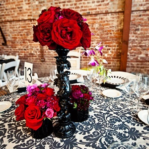Modern black candelabras were topped and surrounded with red roses. Black-and-white damask linens topped tables for a bold look.