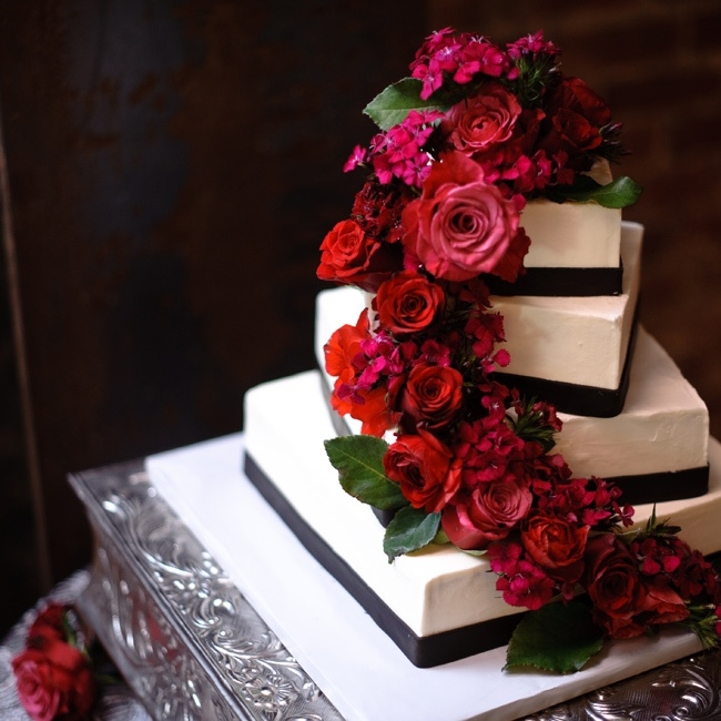 The couple's simple black-and-white cake featured square tiers placed at different angles. Fresh red roses cascaded down the side.