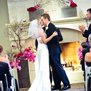 The couple wed in front of a romantic fireplace surrounded by red and fuchsia roses and orchids.