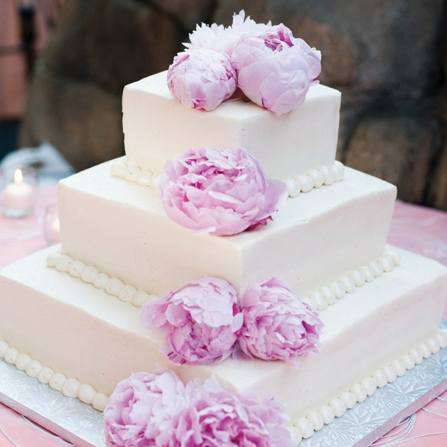 The three-tiered square cake was topped with peonies.