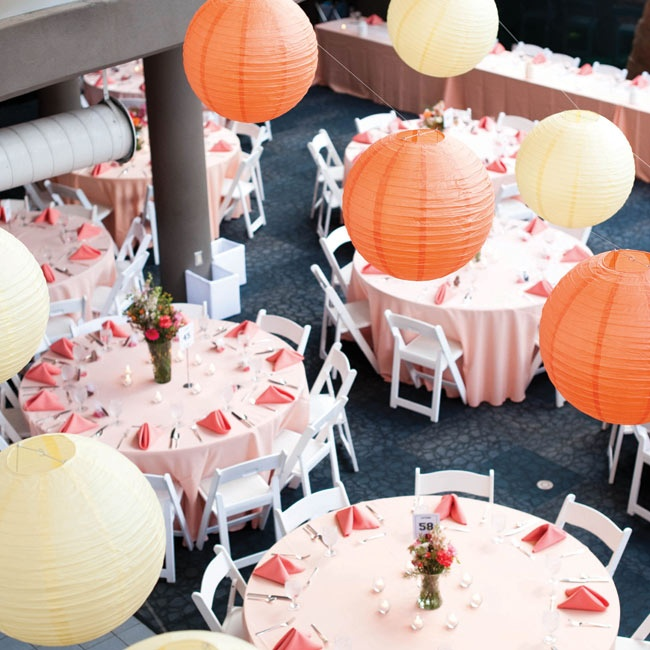 Orange and yellow paper lanterns hung from the ceiling, while peach and coral linens covered the tables.