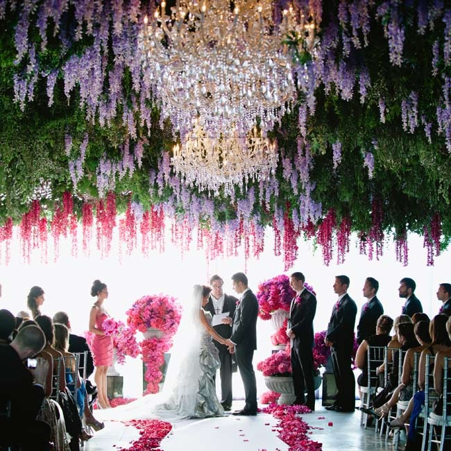 A giant installation of greenery, wisteria and chandeliers hung over the ceremony space.
