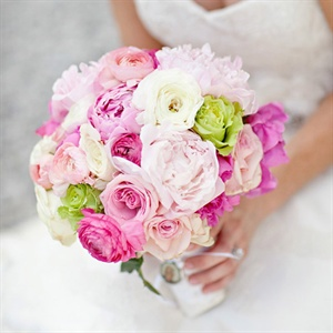 From looking at bridal bouquets Michelle knew that she wanted to have peonies for her bridal bouquet. Her florist, Tina, suggested that she add flowers such as ranunculuses and roses to compliment the peonies. What she ended up with was a soft and luscious flower bouquet which they wrapped in lace from her mother's wedding veil and added a locket t ...
