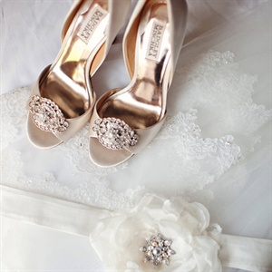 Since the bride's wedding gown didn't have a lot of sparkle elements she opted to add sparkle to her look with her accessories. The bride added a rhinestone brooch to her vanilla colored open toe Badgley Mischka heels and wore a sash with an organza peony flower that had rhinestones and pearls in the center for the right amount of sparkle.