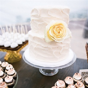 The simple white cake was accented with a yellow rose.