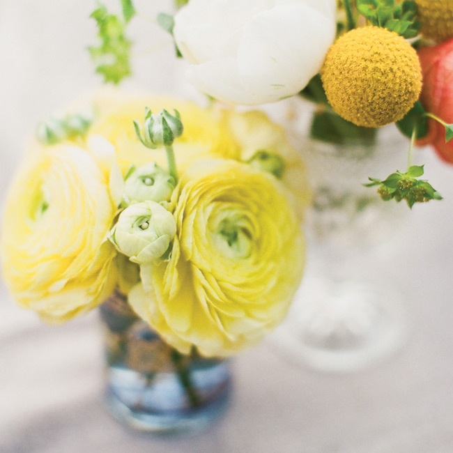 Similar to Alyssa's bouquet, the tables were topped with bright blooms like craspedia and ranunculus.