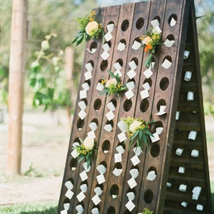 Scrolled escort cards were tucked into the holes of a wooden riddling rack.