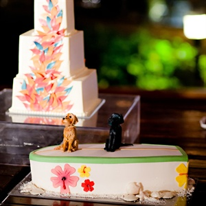 The couple set out two cakes: a square-tiered one with colorful petals, and a surfboard one with replicas of their two dogs on top.