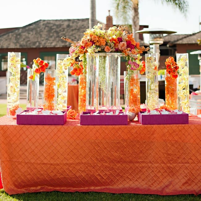 A bright display of submerged orchids in tall vases served as the focal point of the escort card table.