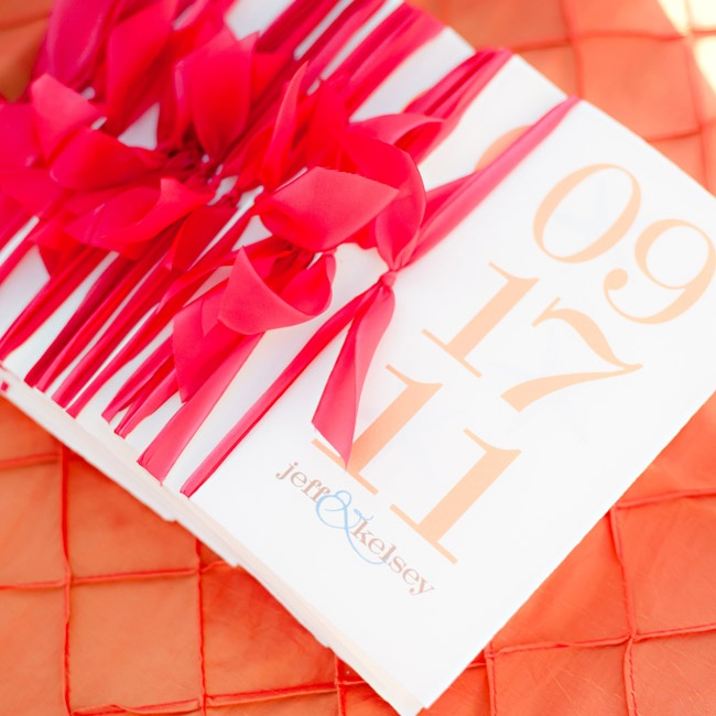 A bold orange font decorated the programs, which were tied with raspberry-colored ribbons.