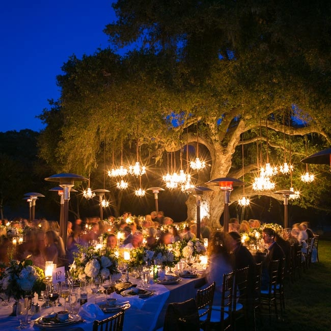 The outdoor reception was lit with chandeliers and well-placed candles, creating a romantic atmosphere.