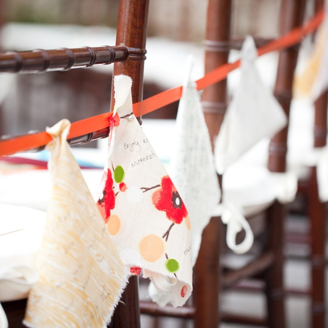 "Instead of a traditional guest book, guests ""signed in"" on these pieces of fabric and pinned them on a ribbon that hung on the las row of ceremony chairs."