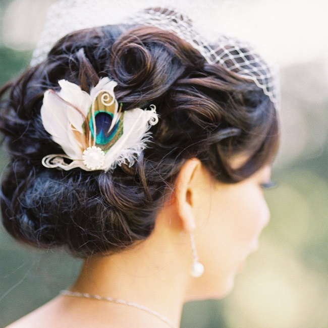 Tianyi wore her hair in a curled updo. For the reception, she traded her cathedral veil for a birdcage veil and added a peacock-feather hairpiece.