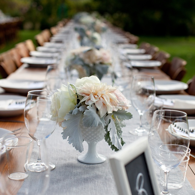 White milkglass urns added a vintage touch to the tables. Gray runners gave the wooden tables a luxe look.