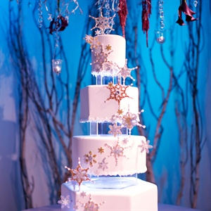 The snow-white cake had alternating hexagonal and round tiers. Handmade snowflakes cascaded down the front, and acrylic spacers were lit with LED lights.