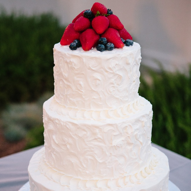 The classic buttercream cake was topped with fresh strawberries and blueberries.
