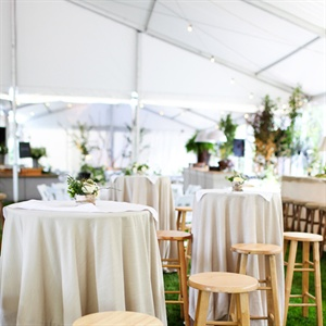 The tent was transformed into different seating areas. One of the areas consisted of high-top tables with wooden stools.