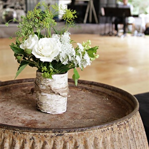 Centerpieces were created using canning jars wrapped with twine in white birch bark that were filled with just picked garden bouquets of flowers