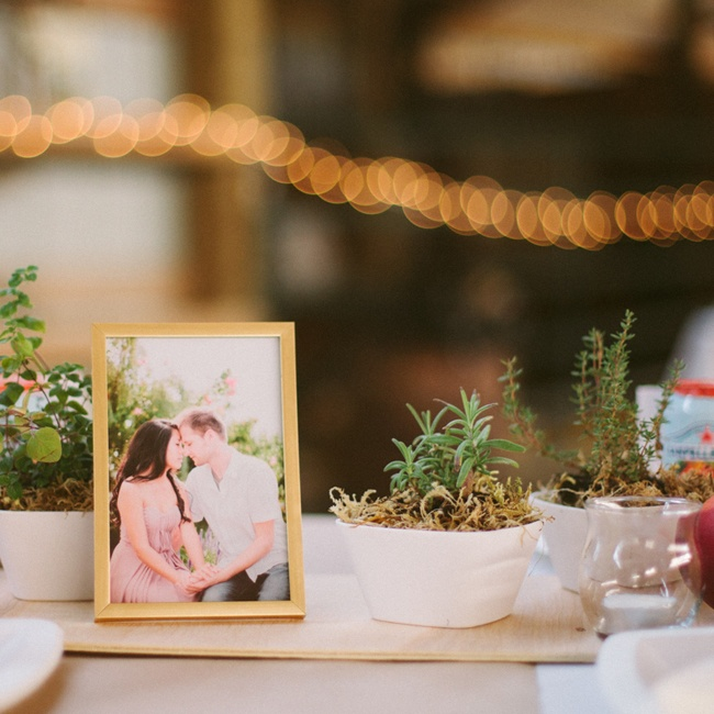 On each table laid an assortment of potted herbs, a golden framed photo of Arlina and Dusty from their engagement session and square white bowls filled with fresh peaches and other fruits.