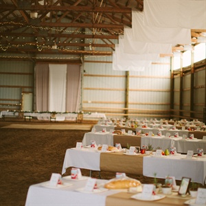 The reception was held in a horse arena with a vaulted ceiling. The couple hung panels of white muslin from the tall beams. The tables were on either sides of an entrance aisle and were family style seating, which paired perfectly with the benches! The dirt aisle led straight to the dance floor and the head table lined the back side of the dance fl ...