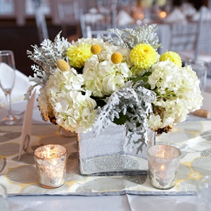 Megan and PJ chose a square crackled mirror vase with yellow caspedias, white hydrangeas, soft yellow dahlias and dusty miller for their centerpieces. Four votive candles surrounded each centerpiece.