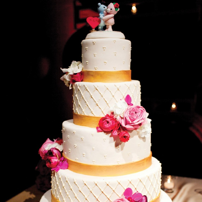 Clusters of fresh flowers adorned the five-tiered ivory fondant cake.