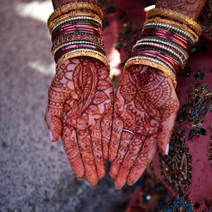 The bride had her hands decorated with elaborate henna designs.
