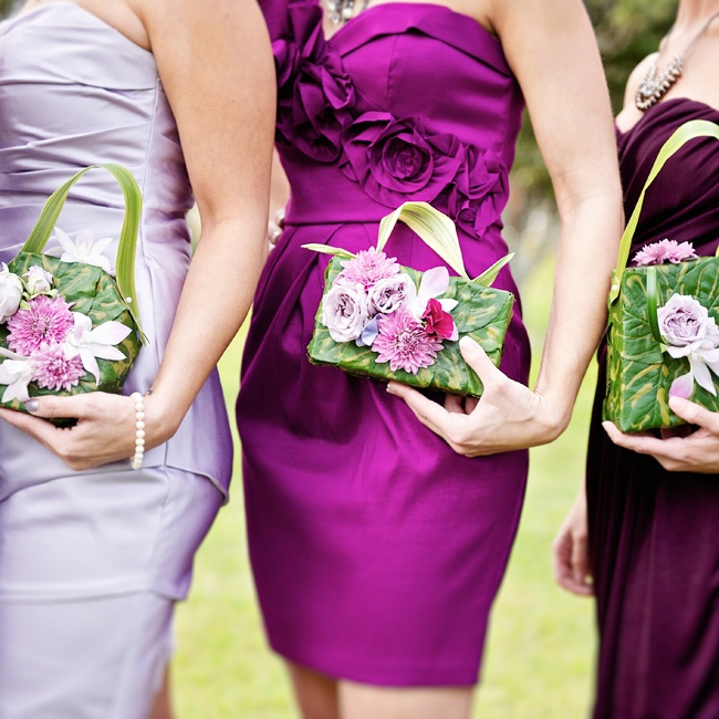 Leigh's bridal party wore their choice of purple hue dresses, pearl jewelry, and carried pill box purses of different shapes made of real leaves and flowers with a leaf handle.