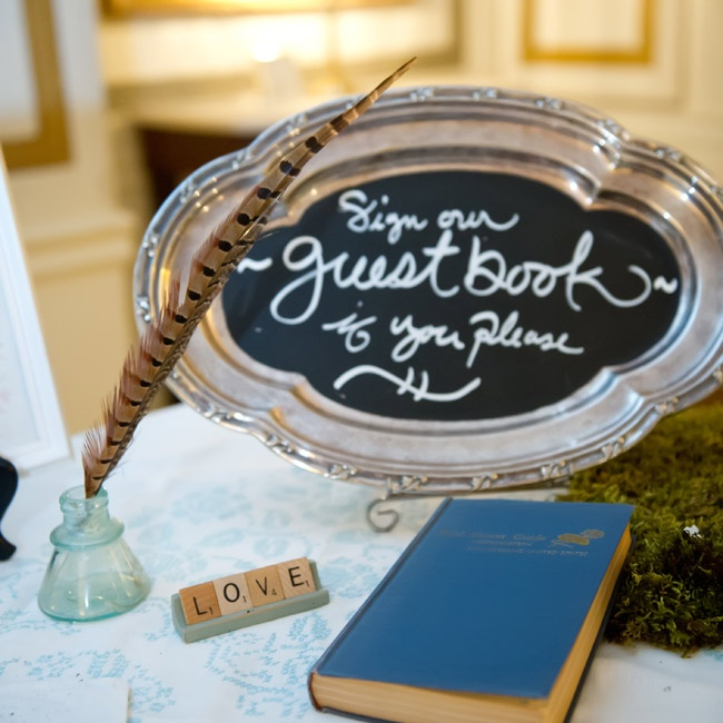 The couple's guest book table was decorated with an antique tray and a vintage wildflower guide and quill.
