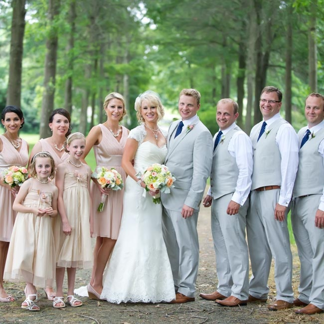The bridesmaids wore pale-pink V-neck dresses, while the groomsmen all matched in gray pants and vests and blue ties.