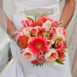 Nicki's Bridal bouquet was an elegant assortment of vibrant blossoms such as garden roses, dahlias and gerbera daisies in different shades of coral. The bouquet was wrapped in alabaster satin ribbon and fastened with crystal pins.
