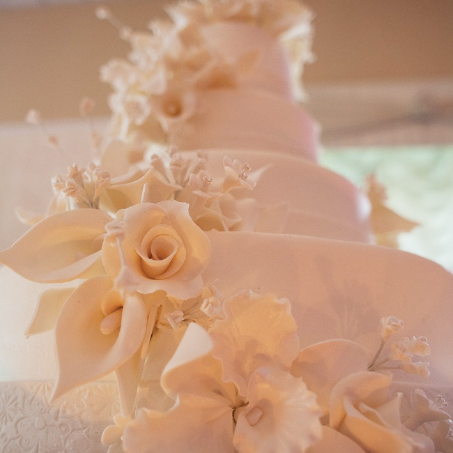 Sugar flowers cascaded down the four-tiered ivory wedding cake.