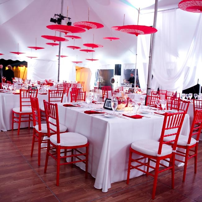 Red chiavari chairs popped against the white linens, while red umbrellas hung overhead for a unique look.